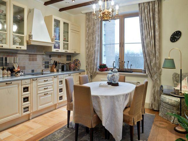 обеденный стол по центру просторной кухни