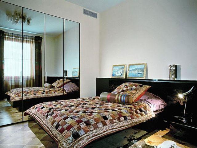 большое зеркало в интерьере маленькой спальни