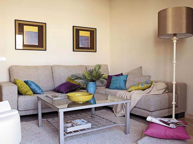 серый диван с яркими подушками смотрится очень стильно