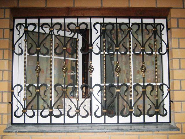 темные кованные решетки на окнах